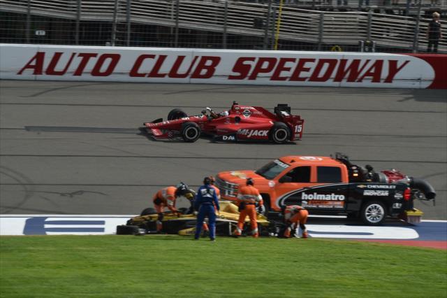 © IndyCar/C.Owens - Rahal en vainqueur passe devant la monoplace détruite de Ryan Briscoe